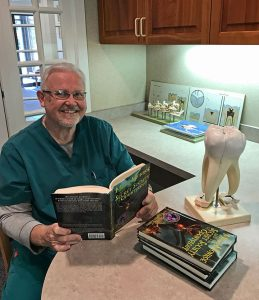 Edward Torba in his dentist office with a copy of his first book, Matt Monroe and the Secret Society of Odontology